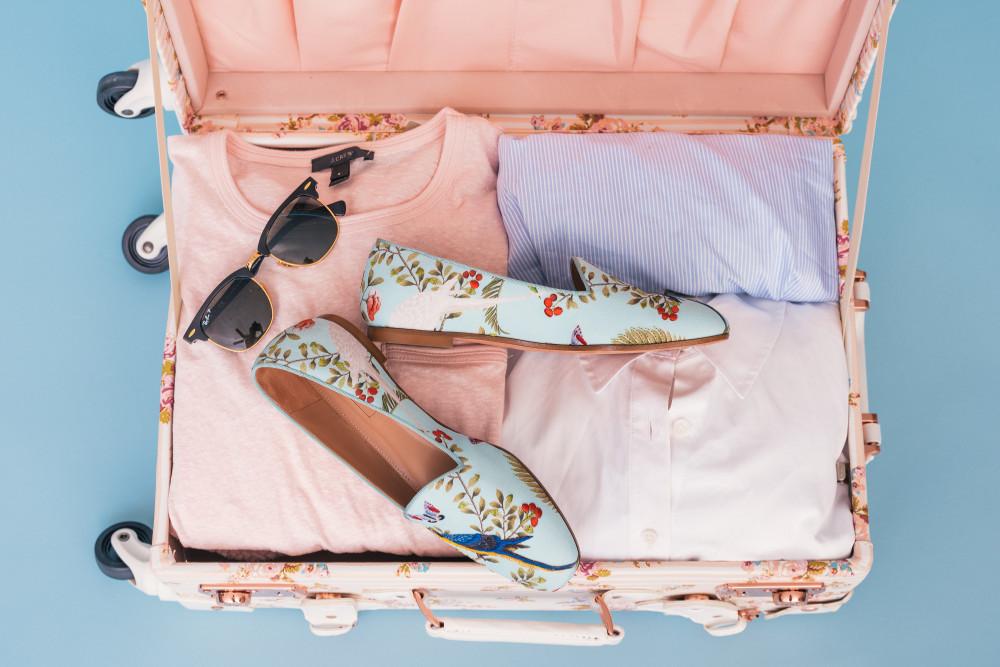 valise avec vêtements lunettes de soleil et chaussures femme