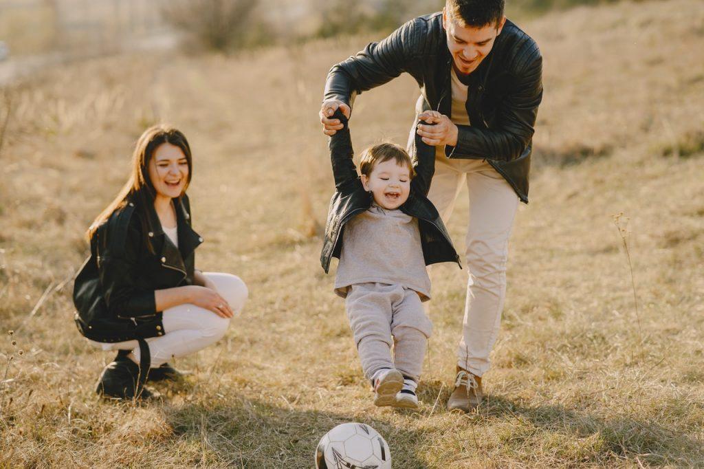 parents qui jouent avec leur enfant au football