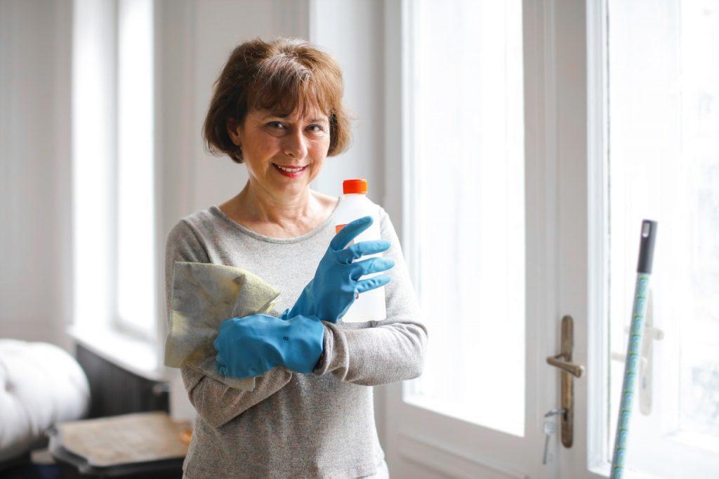 femme de ménage souriante qui des produits en croisant les bras
